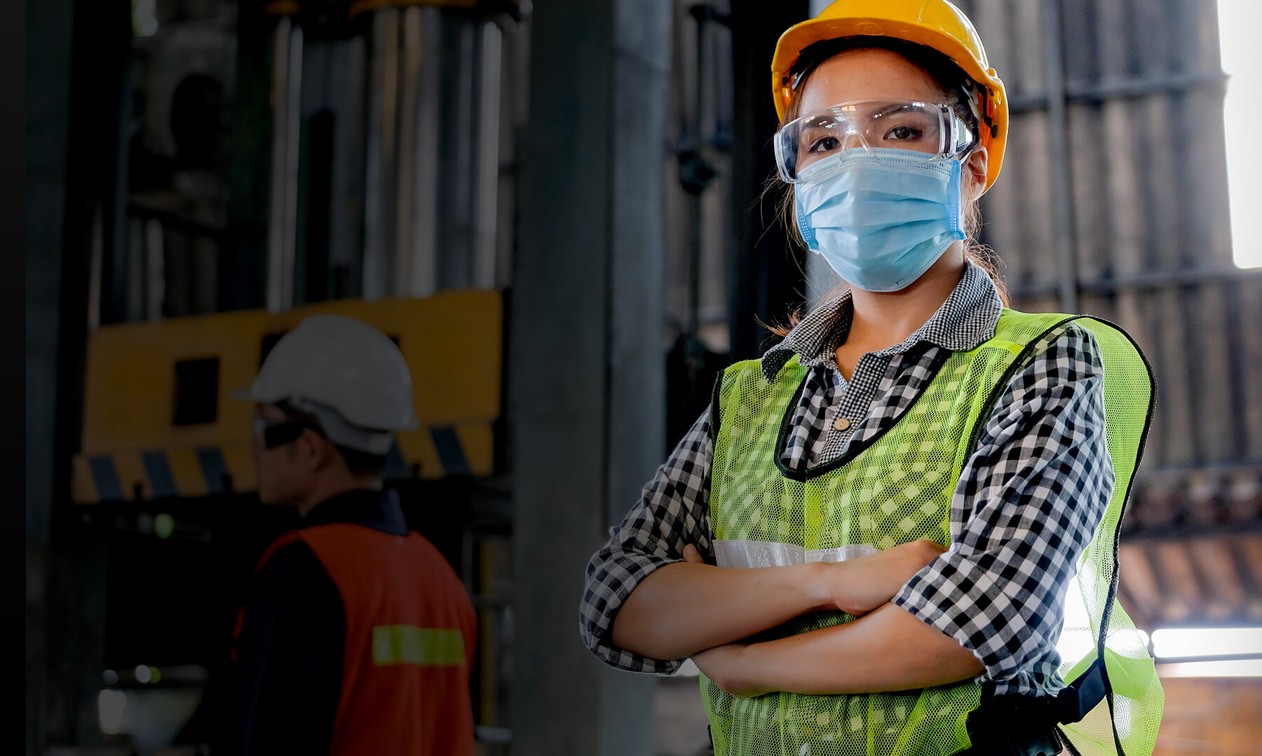 Young woman with mask at manufacturing plant with mask on